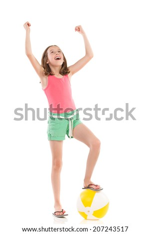 Shouting girl in pink shirt and green shorts posing with a beach ball under her foot. Full length studio shot isolated on white. - stock photo