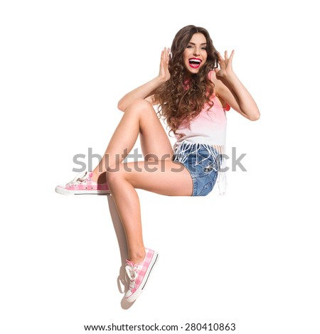 Shouting Girl Sitting On A Banner. Shocked young woman in pink top, jeans shorts and pink sneakers sitting on the white banner. Full length studio shot isolated on white. - stock photo