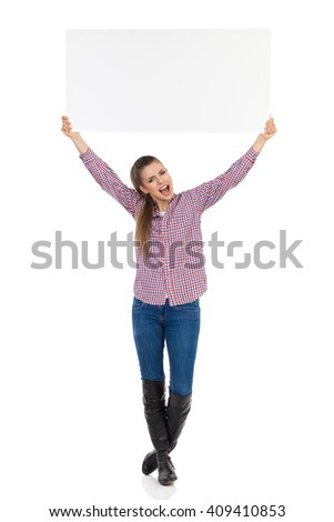 Shouting young woman in jeans, black boots and lumberjack shirt standing and holding white placard above her head. Full length studio shot isolated on white. - stock photo