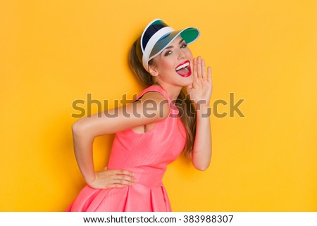 Shouting young woman in pink dress and blue sun visor posing with hand on chin. Three quarter length studio shot on yellow background. - stock photo