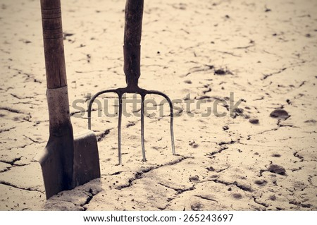 Shovel and pitchfork in the cracked earth in the spring. Old garden tools. - stock photo