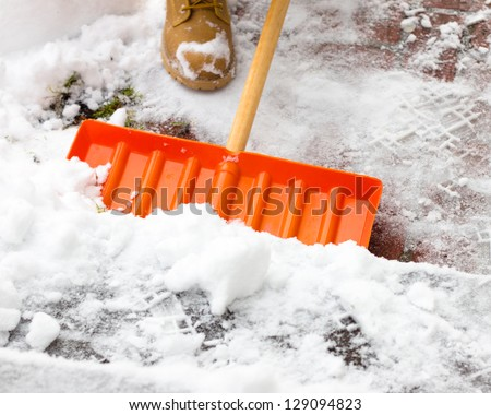 Shovel being pushed through snow - stock photo