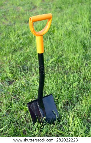 Shovel stuck in the grass lawn - stock photo