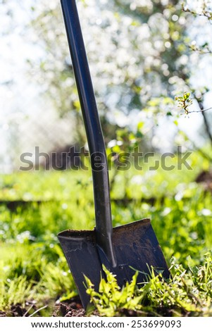 Shovel stuck into the spring ground - stock photo