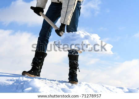 Shovelling snow: removing snow from driveway - stock photo