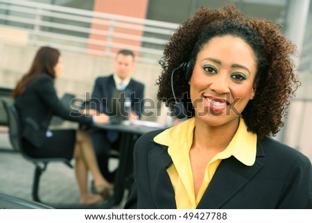 show of african american business woman wiearing headset and her colleagues on the background - stock photo