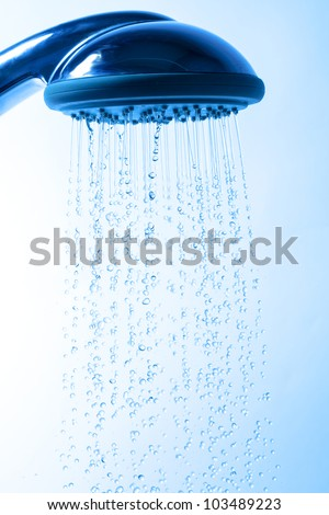 Shower Head with Running Water, Blue background - stock photo