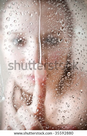 showering woman shot from behind glass - stock photo