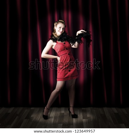 Showgirl Performing On A Theater Stage In Front Of Red Curtains In A Depiction Of A Broadway Cabaret Show - stock photo