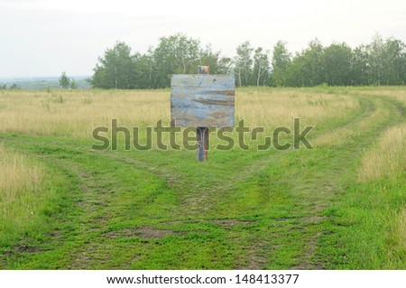 Showing a path splitting into two going with a blank signpost.  - stock photo