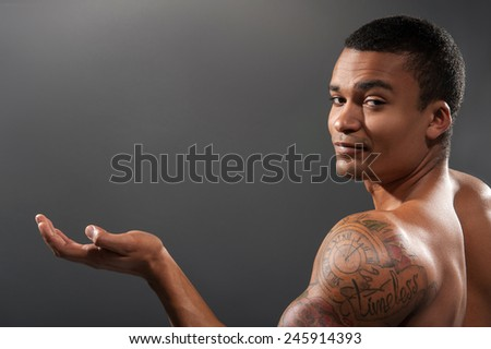 Showing copy space. Rear view of young shirtless African man with muscular body showing copy space and smiling at camera while standing against grey background   - stock photo