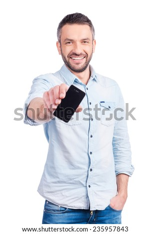 Showing his brand new smart phone. Handsome young man in casual wear showing his smart phone and smiling while standing isolated on white background - stock photo