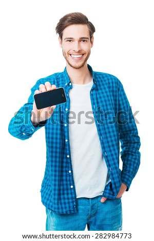 Showing his new smart phone. Cheerful young man stretching out mobile phone and smiling while standing against white background - stock photo