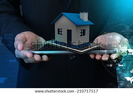 Showing home with smart phone - stock photo