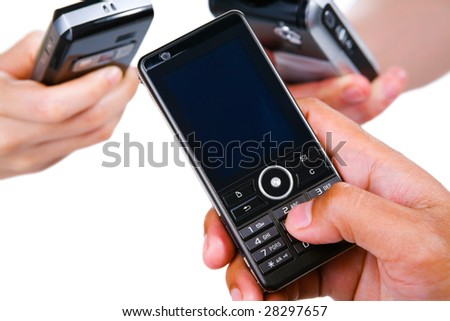 Showing only three hands, each holding cell phone, saving each other contact number in their cell phone. - stock photo