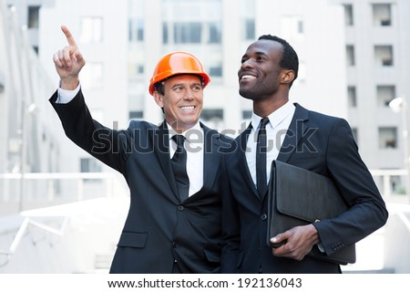 Showing opportunities. Cheerful contractor in hardhat pointing away and smiling while standing together with African businessman - stock photo