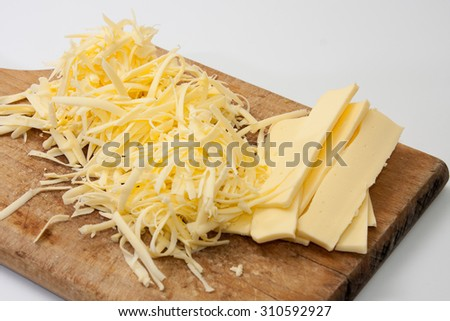Shredded cheese on wooden kitchen board. - stock photo