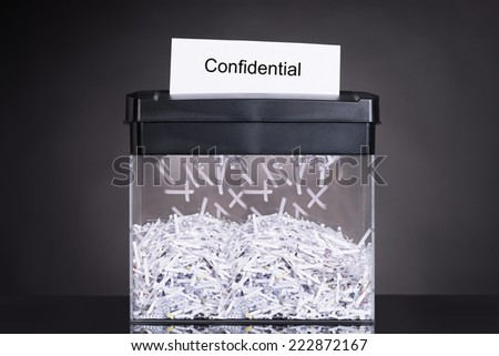 Shredded destroying confidential document over black background - stock photo