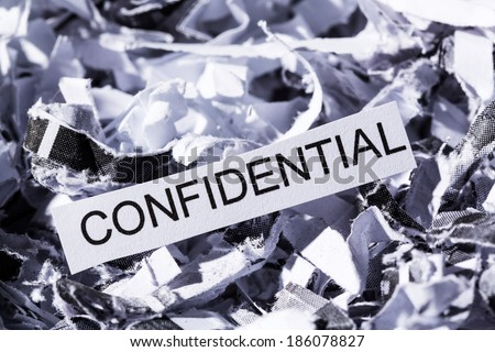 shredded paper tagged confidential, symbol photo for data destruction, banking secrecy and confidentiality - stock photo