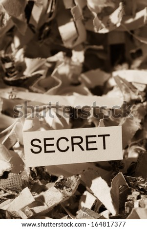 shredded paper tagged with secret, symbol photo for data destruction, banking secrecy and economic espionage - stock photo