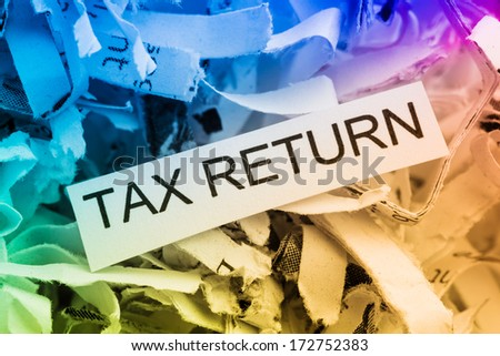 shredded paper tagged with tax return, symbol photo for data destruction, data protection and tax law - stock photo