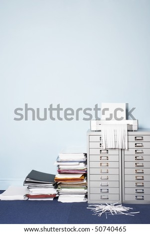 Shredder on file cabinet, stack of paperwork on floor in office - stock photo