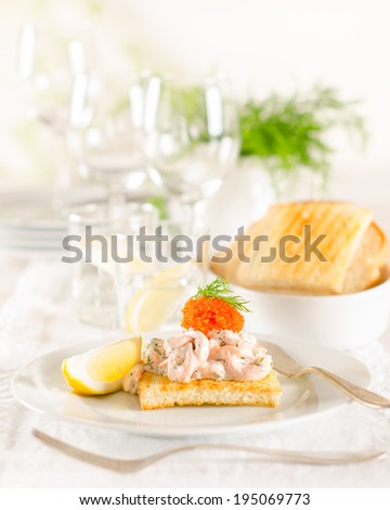 Shrimp and caviar appetizer on white festive table set up - stock photo