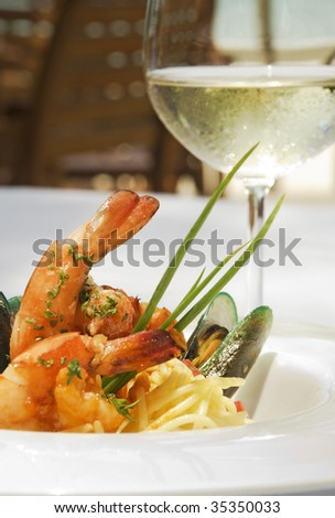 Shrimp and oyster spaghetti served in a white ceramic plate and accompanied with a glass of a white wine. - stock photo