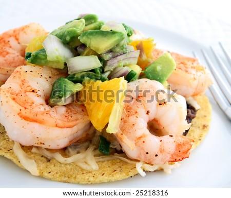 Shrimp and re-fried bean tostada with avocado salsa - stock photo