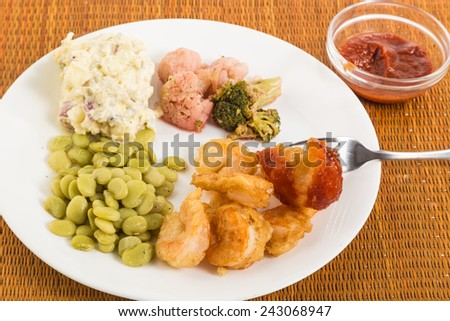 Shrimp battered in beer tempura on plate with beans cauliflower and potato salad.  Shrimp dipped in cocktail sauce. - stock photo