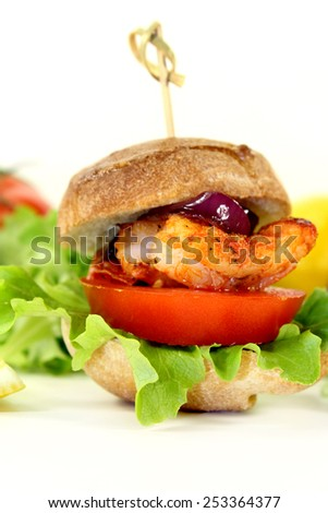 Shrimp burger with tomato, red onion and lettuce - stock photo