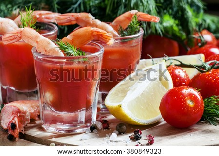 Shrimp cocktail in small glasses, cherry tomatoes, dill, parsley and lemon with salt and spices, selective focus - stock photo