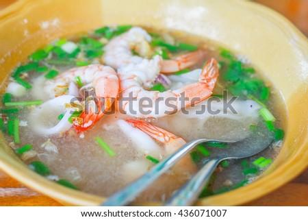 Shrimp porridge,Rice porridge with shrimp in white bowl,Porridge rice with shrimps and fried garlic. white colors fabric background,thai asian - stock photo