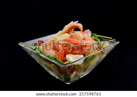 Shrimp salad with cheese, quail egg, greens, tomatoes, watered transparent sauce, served in a glass salad bowl on a black background - stock photo
