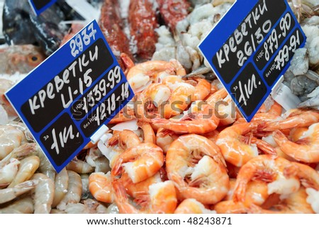 Shrimps on cooled market display, TMs removed from price tags - stock photo