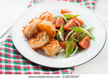 Shrimps (prawns) and fresh snow peas and tomato salad, selective focus - stock photo