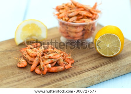 Shrimps. Sea products. Serving of cooked shrimp. Prepared shrimp on wooden blue background. Shrimp from the Black Sea. Snack to beer and wine. Delicious fresh cooked shrimp prepared to eat.  - stock photo