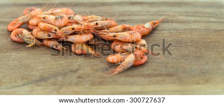 Shrimps. Sea products. Shrimp from the Black Sea. Snack to beer and wine. Serve cooked shrimp on a wooden plank. Delicious fresh cooked shrimp prepared to eat. Cooked shrimps on wooden table. - stock photo