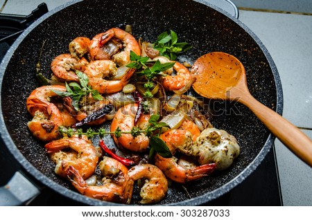 Shrimps served on a pan with fresh herbs - stock photo