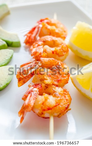 Shrimps skewers with avocado and lemon slices - stock photo