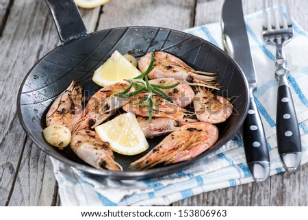 Shrimps with garlich and herbs in a skillet - stock photo