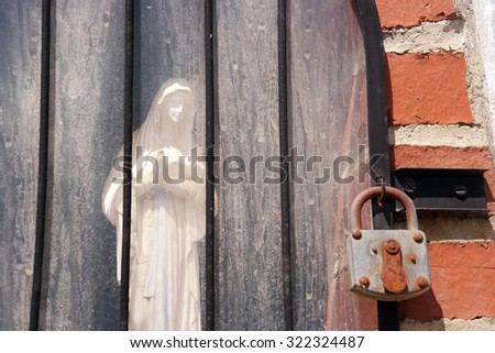 Shrine with Madonna figure behind a locked glass door - stock photo