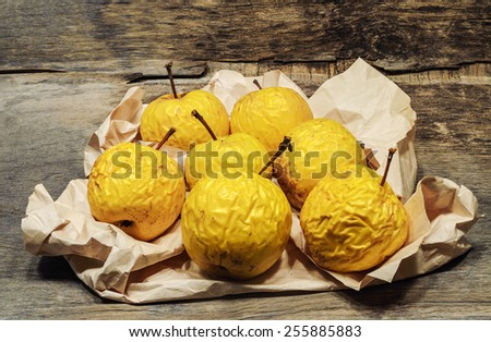 shriveled  yellow  apples on crumpled paper - stock photo