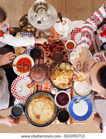 Shrovetide Celebration at home, in the family circle. Set the table with a samovar and pancakes. People in national costumes eating at the table. top view  - stock photo