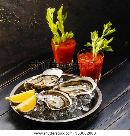 Shucked Oysters Fines de Claire and Bloody Mary cocktail on dark background - stock photo