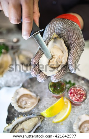 shucking an oyster as water drips out. The oyster opening is in focus and the person hands with oyster plate background. - stock photo