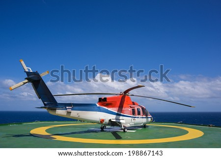 Shut down helicopter on oil rig helipad with blue sky - stock photo