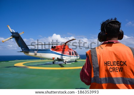 Shut down helicopter with helipad crew on jack up oil rig helipad with blue sky - stock photo