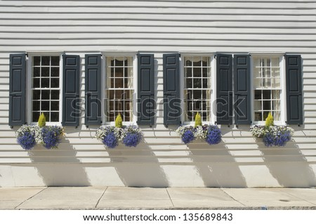 Shuttered windows decorated with flowers and plants in the wall of an eighteenth century house. - stock photo