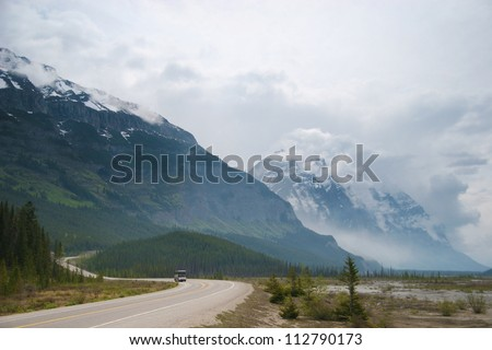 Shuttle bus lumbers up the road to Jasper national park, Alberta, Canada - stock photo